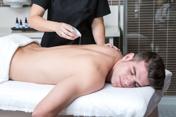 Cosmetologist pouring oil on man's back at spa
