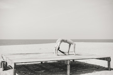 Back view of attractive fit woman sport stretching over the sea outdoor sunny background. Black and white photography
