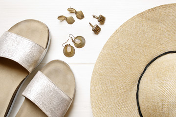 golden earrings, straw hat, slippers- summer accessories on wooden background