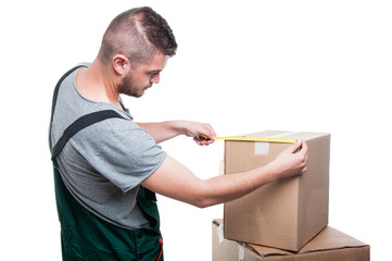 Mover guy measuring cardboard box with ruler tape