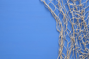 Top view of Fishnet on blue wooden background