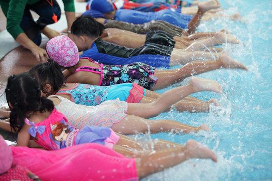 kid learning to swim in swimming pool class