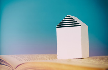 small house model over open book. selective focus