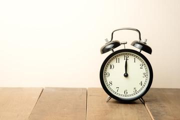 black vintage alarm clock close to the window present twelve o'clock, midday or midnight Fotoväggar