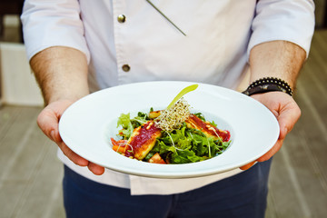 Beautiful fresh Salad with halloumi cheese grilled in the hands of the chefs are men