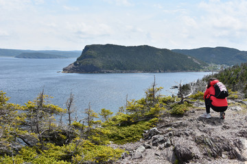 Young female tourist admiring calm bay in Newfoundland, Canada