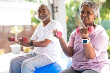 Portrait of smiling couple lifting dumbbells