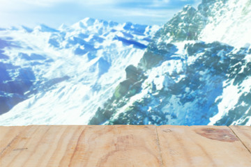 Wooden board empty table in front of blurred background of snow mountain with sunray and lens flare