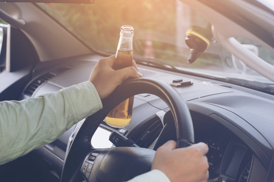 """Drunk young man drives a car with a bottle of beer. This is a campaign picture of """"Don't Drink for Drive."""".selectove focus"""