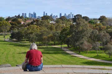 Red shirted man looking at the skyline of Melbourne