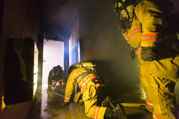 Firefighter training exiting the building with a victim