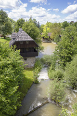 Croatian village of Rastoke by a river canyon with wooden houses in a green landscape with trees and a waterfall, Croatia