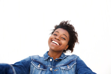Close up smiling young afro american girl taking selfie against white background