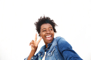 Close up cheerful young woman taking selfie with peace sign