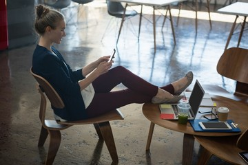 Businesswoman using smart phone while relaxing on chair at office