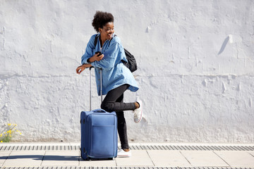 Full length young black female traveler standing with luggage and looking back