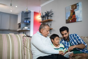 Father and grandfather pointing on tablet used by boy