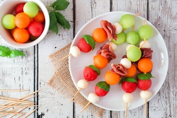 Plate of delicious summer fruit skewers with melon, cheese and prosciutto on a rustic white wood background