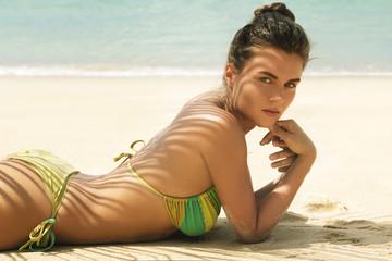 Woman is lying on the beach under palm leaf