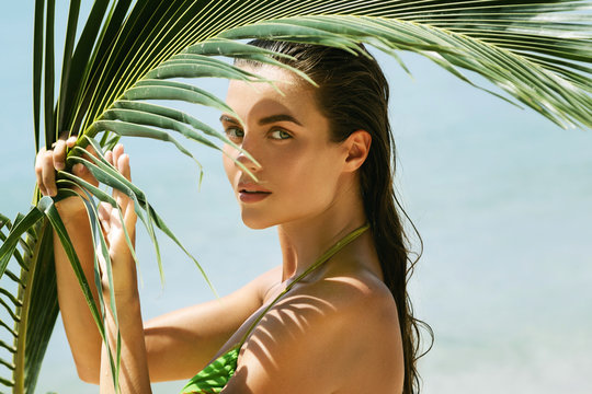 Beautiful woman with a palm leaf on the beach