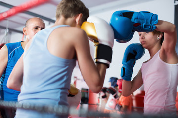 Young sportsman exercising at boxing with instructor