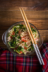 Noodles with vegetables on a wooden background