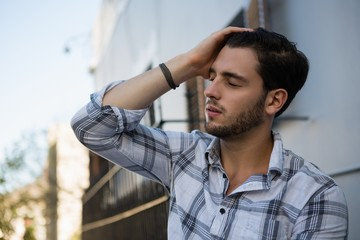 Tensed man sitting by wall