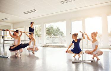 Teacher watching little girls practicing ballet