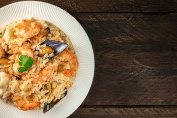 Seafood risotto on dark rustic background with copyspace
