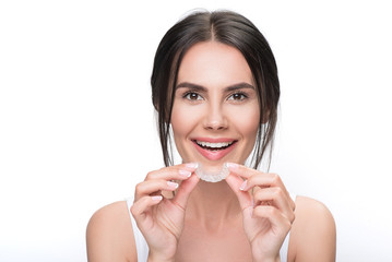 Excited young woman holding clear aligner