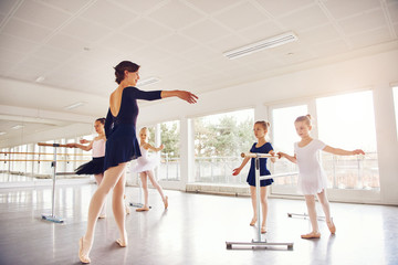 Woman practicing with group of little ballerinas in class