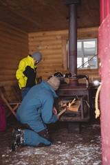 Man putting log into wood burning stove