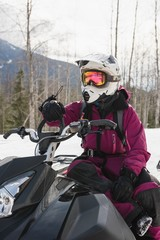 Woman relaxing on snowmobile