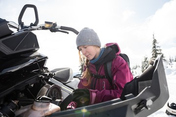 Woman repairing snowmobile on a sunny day