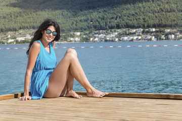 portrait of a beautiful young  woman with blue dress sitting on a pier on the beach .Summer holiday