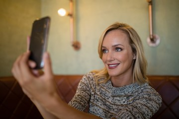 Beautiful woman taking selfie on mobile phone in bar