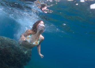 Beautiful healthy girl swims in the sea.