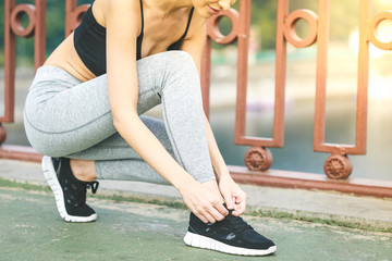 Girl runner tying laces for jogging her shoes on road in a park. Running shoes, Shoelaces, Urban jogger, Exercise concept. Sport lifestyle. close up of woman tying shoelaces outdoors