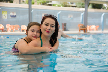 Smiling beautiful woman and her cute child in the pool. Portrait of a happy family relax - having fun together.
