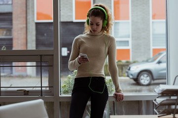 Female executive listening music on mobile phone