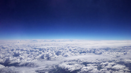 Flying over the clouds. Clouds and skyline horizon panoramic view.