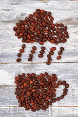 Raindrops from coffee beans. Cup from coffee, wooden background.