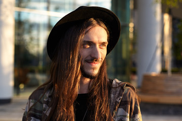 Outdoor summer portrait of fashionable good-looking young Caucasian man with beard and long hair wearing trendy outfit and black hat smiling, enjoying sunny weather, standing in urban surroundings