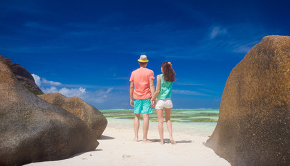 back view of happy young couple having fun by the beach. Seychelles. La Digue island. Anse Source D'Argent