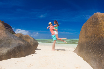 happy young couple having fun by the beach. Seychelles. La Digue island. Anse Source D'Argent