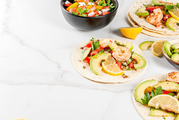 Seafood. Mexican food. Tortilla tacos with traditional homemade salsa salad, parsley, fresh lemon, avocado and grilled shrimp pawns. On a white marble background. Copy space