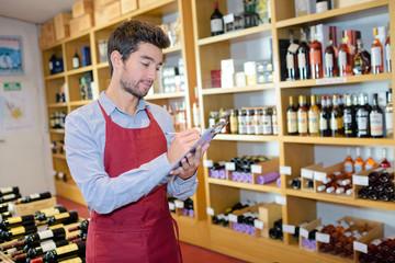 seller wearing apron writing on clipboard in wine store