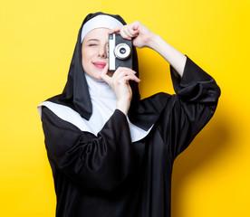 Young happy nun with vintage photo camera
