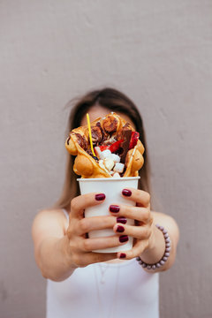 Young woman holding bubble waffle with fruits, chocolate and marshmallow, selective focus