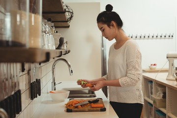 Woman peeling vegetables in kitchen sink